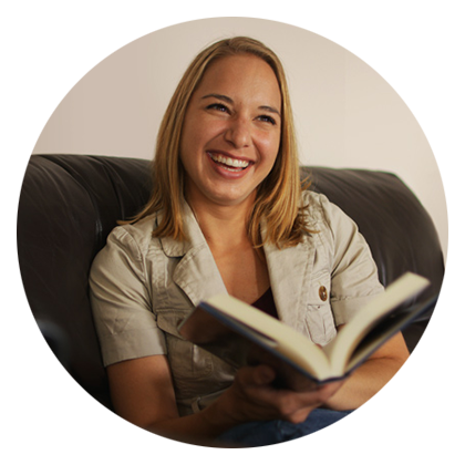 iUniverse author Julie Hockley sitting on a couch holding a book, with cheerful laughter.