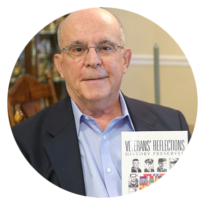 iUniverse author William Graser holding his published book Veterans' Reflections: History Preserved.